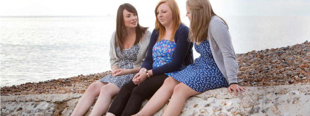 Teenage friends sitting on a beach