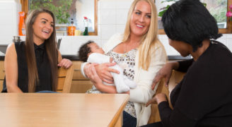 Three women and a baby sitting in a kitchen