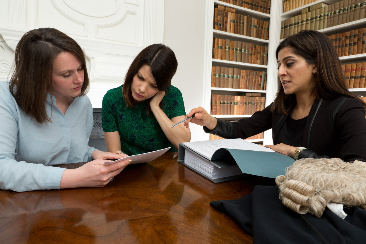 A Refuge IDVA, a client and a lawyer sitting round a table.