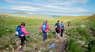 A group of people walking in single file on the Yorkshire Three Peaks challenge