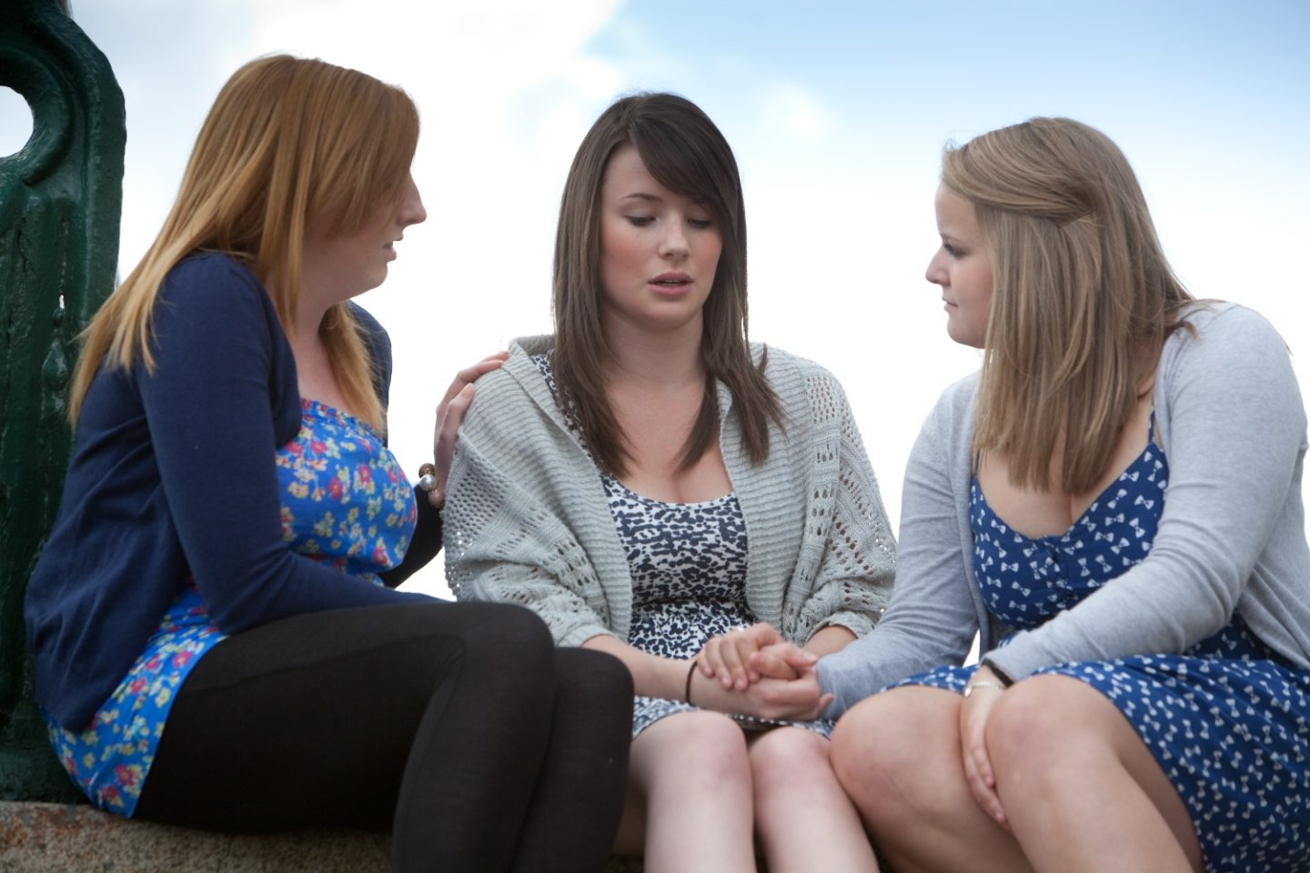 Three girls sitting together. Two of the girls are consoling the other and holding her hands.
