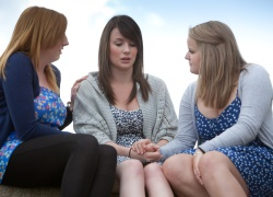 Three young women sitting together, holding hands