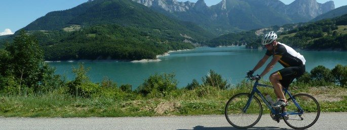 A male cyclist riding through stunning landscape on the Geneva to Nice Cycle