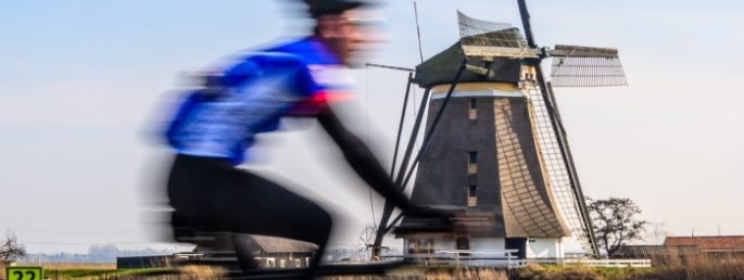A cyclist on the London to Amsterdam Cycle riding past a windmill.