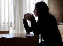 A woman sat at a table holding a mug looking out of the window.