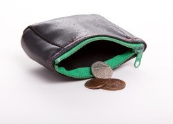 An open purse with money falling out