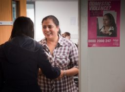 A woman greets another woman at the door of Refuge's Gaia centre