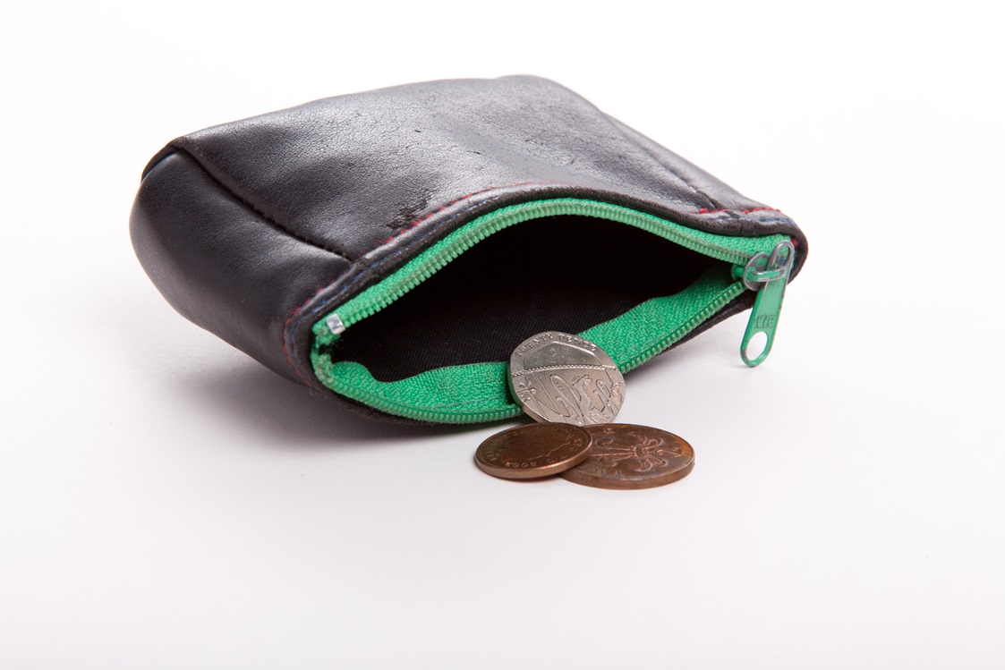 Open purse with money falling out