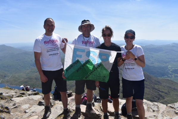 Four employees fro HMP East Sutton holding a flag, wearing Refuge tshirts, at the top of a mountain.