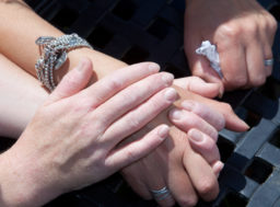 A woman holds another woman's hand as a gesture of support.