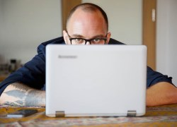 A man sits behind the screen of a laptop