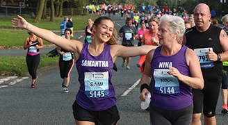 Two women running the manchester marathon with runners behind them. The younger woman has her arms out stretched in celebration.