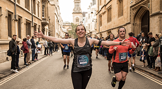 A women as part of a race runs through a historic street in Oxford, her arms are outstretched in excitement