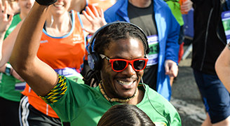 A man in red sunglasses with a smile on his face raises his hand as part of a crowd of runners
