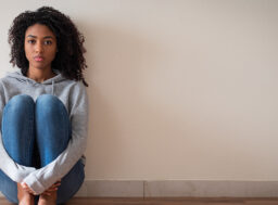 A young women sit on the floor holding her knees looking anxious